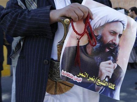 A Shi'ite protester carries a poster of Sheikh Nimr al-Nimr during a demonstration outside the Saudi embassy in Sanaa October 18, 2014. REUTERS/Khaled Abdullah/Files