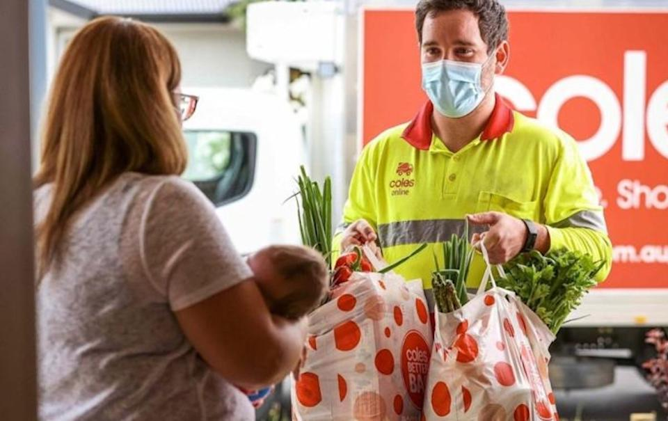Coles delivery driver delivering groceries to woman with baby. Source: Coles