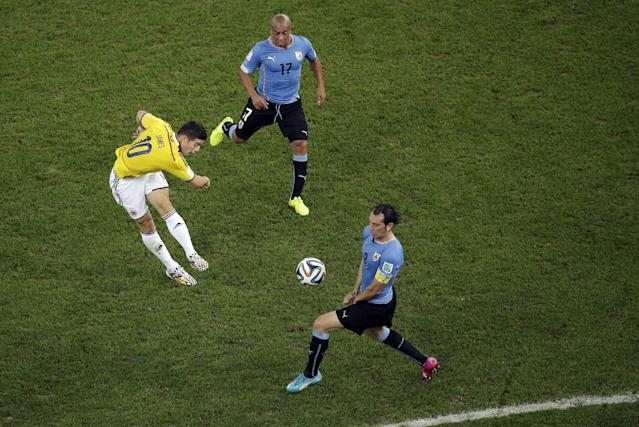 Colombia's James Rodriguez, left, scores the opening goal past Uruguay's Diego Godin, front, as Uruguay's Egidio Arevalo Rios gives chase during the World Cup round of 16 soccer match between Colombia and Uruguay at the Maracana Stadium in Rio de Janeiro, Brazil, Saturday, June 28, 2014. (AP Photo/Felipe Dana, pool)