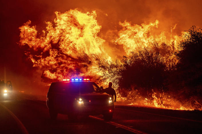 Flames lick above vehicles on Highway 162 as the Bear Fire burns in Oroville, Calif., on Wednesday, Sept. 9, 2020. The blaze, part of the lightning-sparked North Complex, expanded at a critical rate of spread as winds buffeted the region. (AP Photo/Noah Berger)