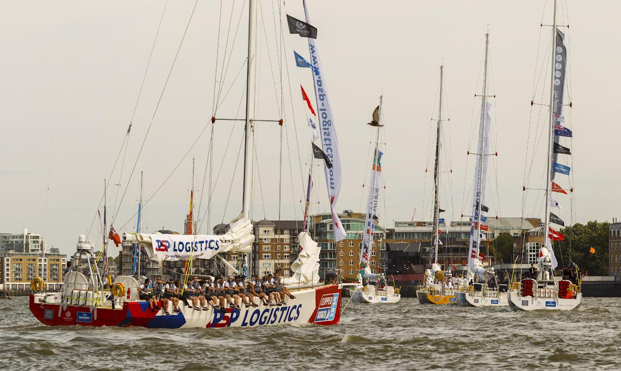 The fleet of twelve Clipper Round the World Race yachts head downstream from Tower Bridge during the start of the Clipper Round the World Race at St Katharine Docks, London.