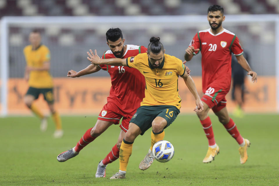 Oman's Omer Talib Ahmed Fazari, right , fights for the ball with Australia's Aziz Behich during a FIFA World Cup group B qualifying soccer match between Australia and Oman in Doha, Qatar, Thursday, Oct. 7, 2021. (AP Photo/Hussein Sayed)