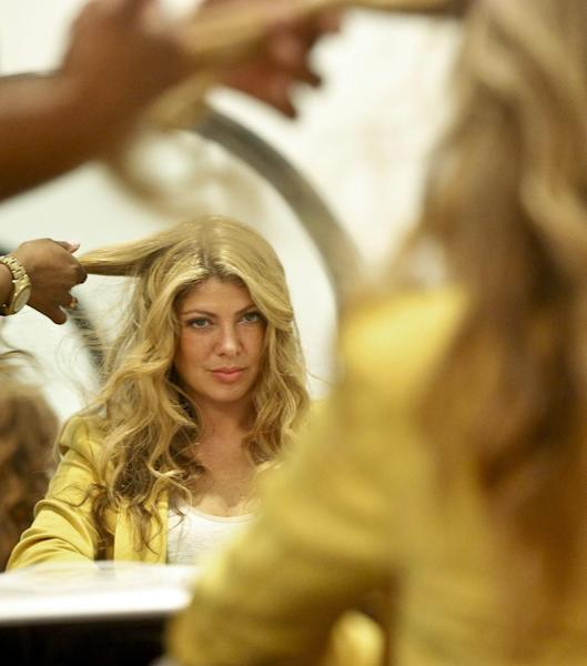 This May 21, 2013 photo shows Alisha Levine with a wavy beach-like hairstyle at Dream Dry salon in New York. When it comes to hair, the grass often seems greener on the other side, but experts say both curly and straight looks require a little work. (AP Photo/Bebeto Matthews)