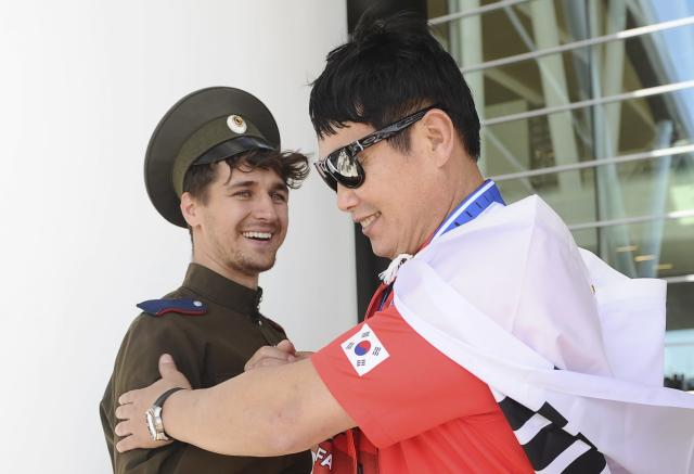 Soccer Football - World Cup - Group F - South Korea v Mexico - Rostov-on-Don, Russia - June 23, 2018. A supporter of South Korea greets a representative of a local Cossack community during a welcoming ceremony before the match. REUTERS/Sergey Pivovarov