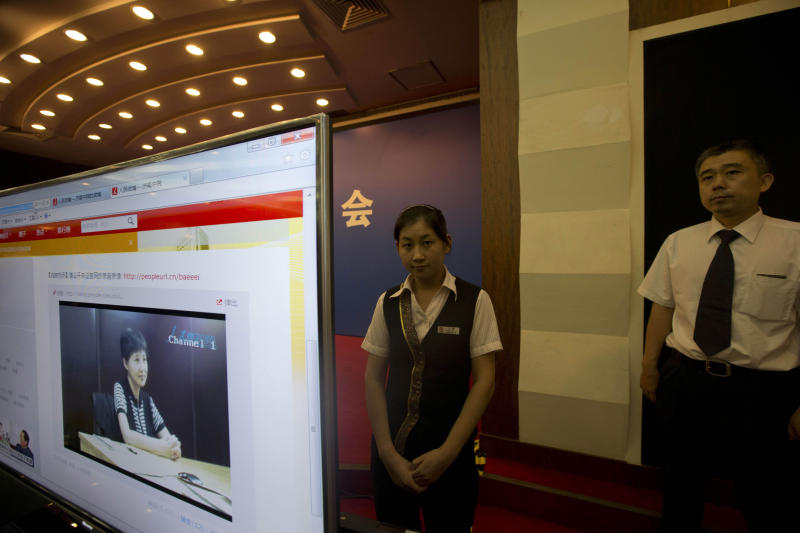 Hotel staff members stand near a display showing an online pre-recorded testimony by Gu Kailai, wife of former Chinese politician Bo Xilai before a press conference held at a hotel near the Jinan Intermediate People's Court in Jinan in eastern China's Shandong province on Friday, Aug. 23, 2013. Bo is accused of corruption and interference in the investigation of his wife's murder of a British businessman. (AP Photo/Ng Han Guan)