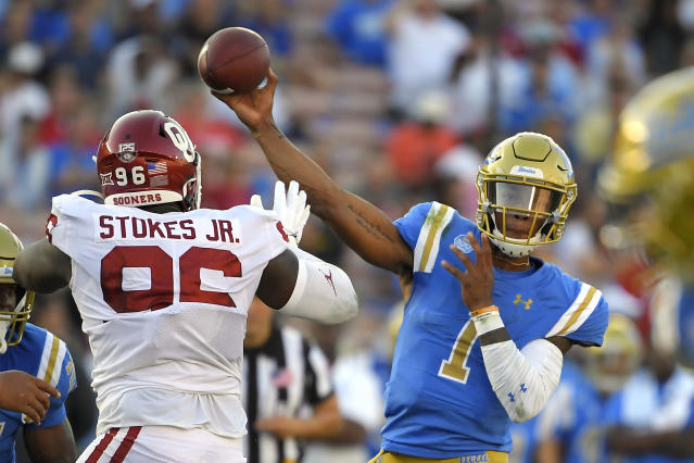 UCLA quarterback Dorian Thompson-Robinson, right, passes while under pressure from Oklahoma defensive lineman LaRon Stokes during the first half of an NCAA college football game Saturday, Sept. 14, 2019, in Pasadena, Calif. (AP Photo/Mark J. Terrill)
