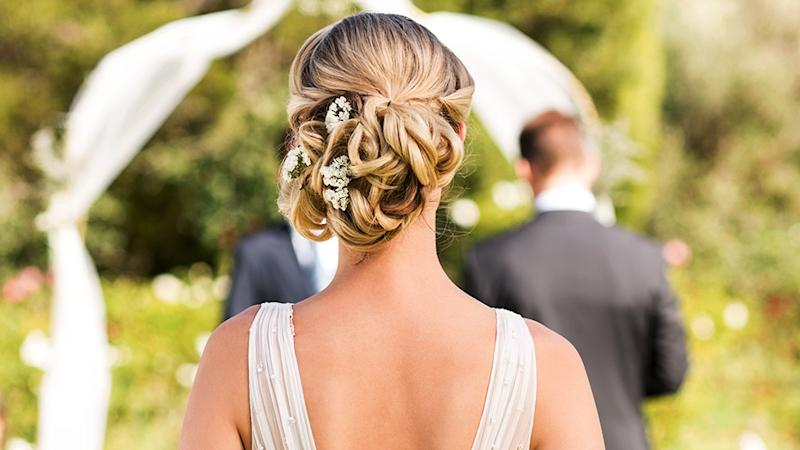 woman with bridal hair do pictured shoulder-up from behind with baby's breath in hair and sheer white straps
