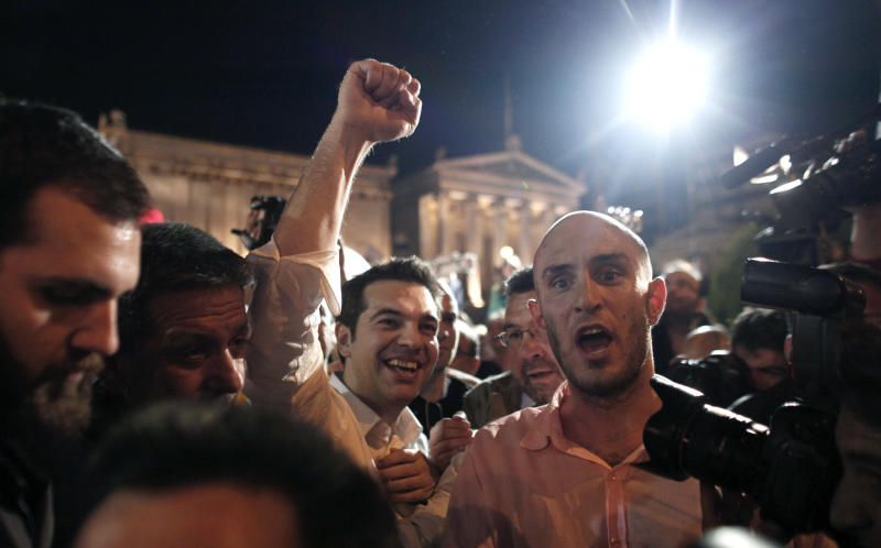 Left Coalition party leader Alexis Tsipras greets supporters with a clenched fist, in central Athens after elections on Sunday, May 6, 2012. Tsipras was projected to come second in the poll, behind the front-runner conservatives, on a pledge to cancel Greece's bailout agreements. (AP Photo/Kostas Tsironis)