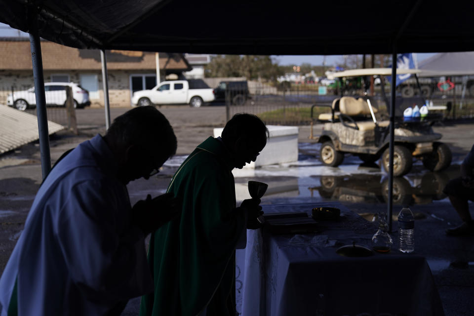 The Rev. Luke Nguyen, right, celebrates Mass in a flood damaged parking lot in the aftermath of Hurricane Ida, Sunday, Sept. 5, 2021, in Jean Lafitte, La. The service was held in a parking lot after St. Anthony Catholic Church was flooded in the hurricane. (AP Photo/John Locher)