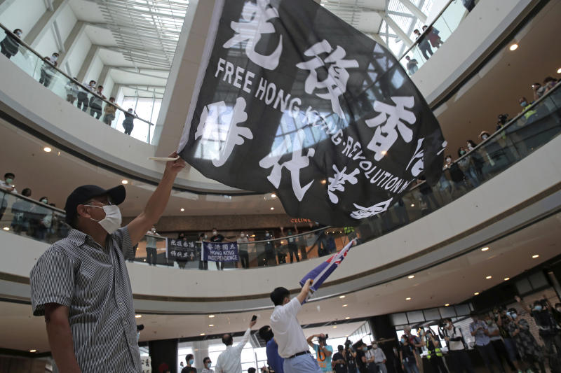 Protesters wave flags in a shopping mall during a protest against China's national security legislation for the city, in Hong Kong, Friday, May 29, 2020. The British government says t it will grant hundreds of thousands of Hong Kong residents greater visa rights if China doesn't scrap a planned new security law for the semi-autonomous territory. U.K. Foreign Secretary Dominic Raab said about 300,000 people in Hong Kong who hold British National (Overseas) passports will be able to stay in Britain for 12 months rather than the current six. (AP Photo/Kin Cheung)