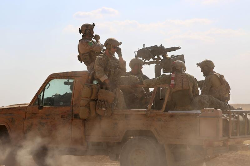 Armed men in uniform identified by Syrian Democratic Forces as US special operations personnel ride in a pickup truck in the village of Fatisah in the northern Syrian province of Raqa on May 25, 2016