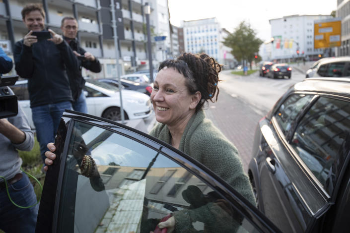 Polish author Olga Tokarczuk smiles as she arrives for a press conference in Bielefeld, Germany, Thursday, Oct 10, 2019. Tokarczuk has been named recipient of the 2018 Nobel Prize in Literature, Thursday. Two Nobel Prizes in literature were announced Thursday after the 2018 literature award was postponed following sex abuse allegations that rocked the Swedish Academy at that time. (Friso Gentsch/dpa via AP)