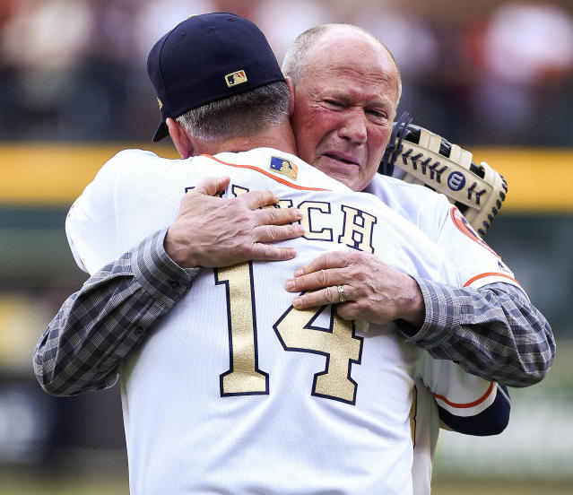 Rich Dauer embraces A.J. Hinch after his first pitch. (AP)