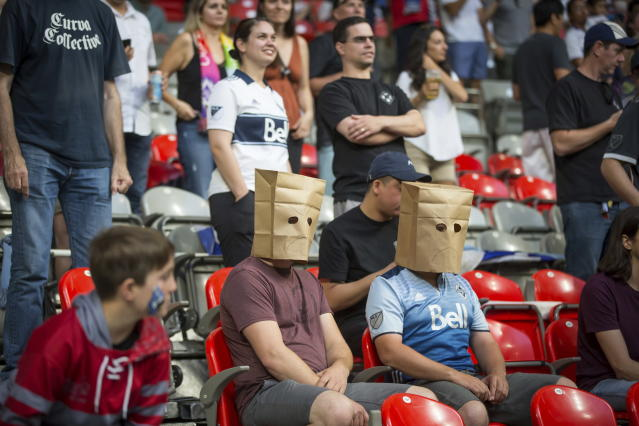 A Vancouver Whitecaps supporters wear paper bags on their heads as the Whitecaps and the San Jose Earthquakes play an MLS soccer match in Vancouver, British Columbia, Saturday July 20, 2019. (Darryl Dyck/The Canadian Press via AP)