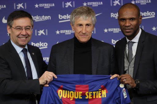 Soccer coach Quique Setien poses with FC Barcelona's President Josep Maria Bartomeu, left, and director of football Eric Abidal, right, while being officially introduced as the club's new coach at the Camp Nou stadium in Barcelona, Spain, Tuesday, Jan. 14, 2020. Barcelona made a rare coaching change midway through the season, replacing Ernesto Valverde with former Real Betis manager Quique Setien on Monday. (AP Photo/Emilio Morenatti)