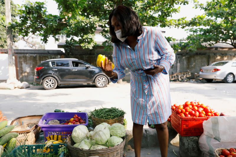 Melanie Igbe, head chef at Cafe de Elyon, shops for vegetables at a street market in Victoria Island, in Lagos
