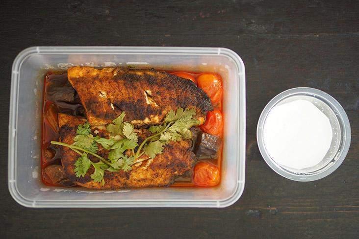 The fish is packed neatly with the eggplant and tomatoes underneath