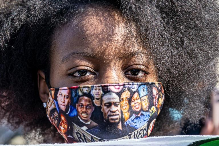 A woman wearing a mask with a picture of George Floyd and other African-Americans killed by police