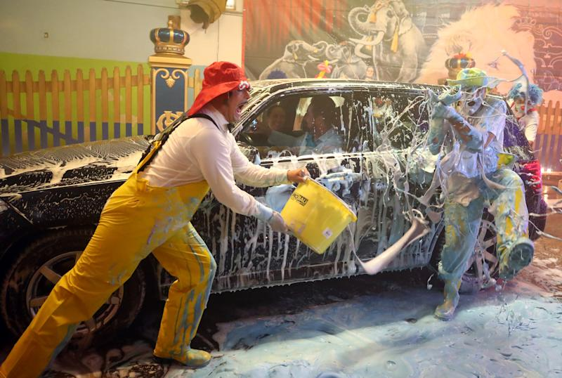 Clowns of the circus Krone joke around in the circus own car wash to bring joy to the people during the playing ban due to the coronavirus disease (COVID-19), in Munich, Germany, August 20, 2020. REUTERS/Michael Dalder