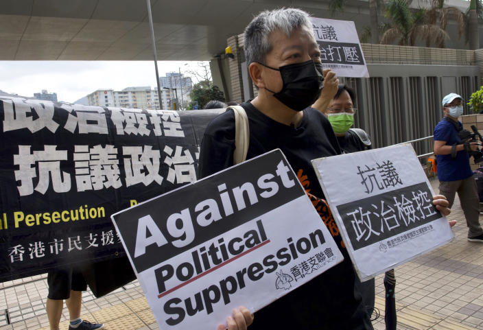 Pro-democracy activist Lee Cheuk-yan, center, holds placards as he arrives at a court in Hong Kong Thursday, April 1, 2021. Seven pro-democracy advocates, including media tycoon Jimmy Lai and veteran of the city's democracy movement Martin Lee, are expected to be handed a verdict for organizing and participating in an illegal assembly during massive anti-government protests in 2019 as Hong Kong continues its crackdown on dissent. (AP Photo/Vincent Yu)