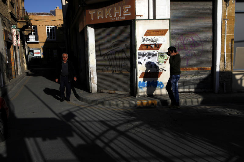 People walk at the old city of capital Nicosia, Cyprus, Saturday, March 23, 2013. Politicians in Cyprus were racing Saturday to complete an alternative plan raising funds necessary for the country to qualify for an international bailout, with a potential bankruptcy just three days away. (AP Photo/Petros Karadjias)