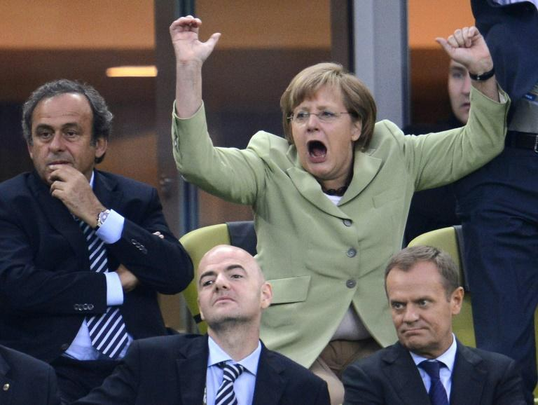 Merkel, celebrating a goal at the 2012 Euro 2012 championships, is known for her football fervour