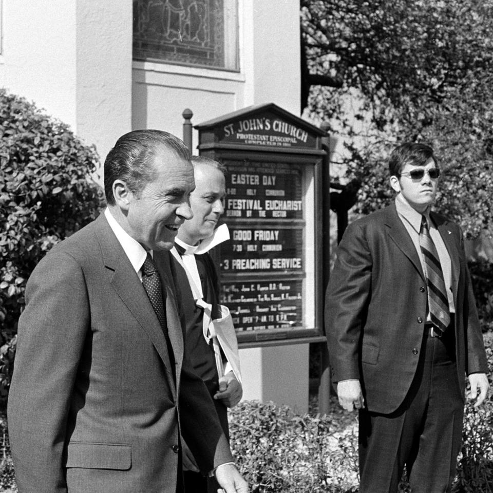 FILE - In this April 1971 file photo, President Richard Nixon, left foreground, walks with Rev. John C. Harper, after attending a Good Friday services at St. John's Episocpal Church near the White House. Every president since James Madison has crossed Lafayette Square to worship at St. John's, the pale yellow Episcopal church within sight of the White House. (AP Photo/Charles Tasnadi)