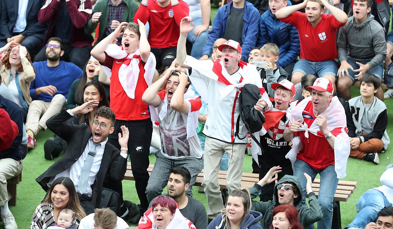 <p>Happy and glorious: Fans decked out in St George's flags and England kits sing their hearts out for the Three Lions. (PA) </p>