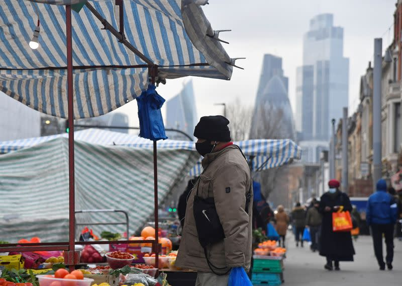 People shop at market stalls, with skyscrapers of the CIty of London financial district seen behind, in London