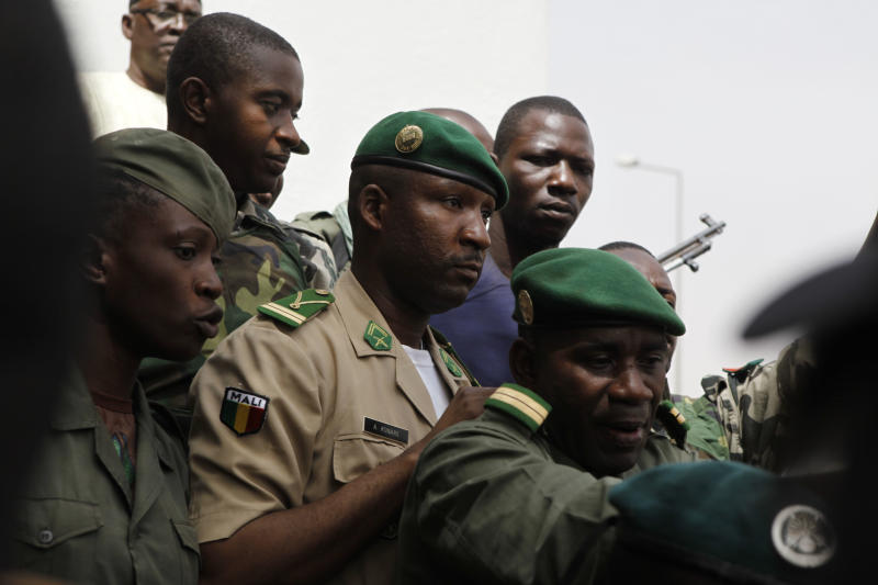 Coup leader Amadou Haya Sanogo, center, is surrounded by security as he arrives to address supporters, as thousands rallied in a show of support for the recent military coup, in Bamako, Mali Wednesday, March 28, 2012. The body representing nations in western Africa has suspended Mali and has put a peacekeeping force on standby in the most direct threat yet to the junta that seized control of this nation in a coup last week. (AP Photo/Rebecca Blackwell)