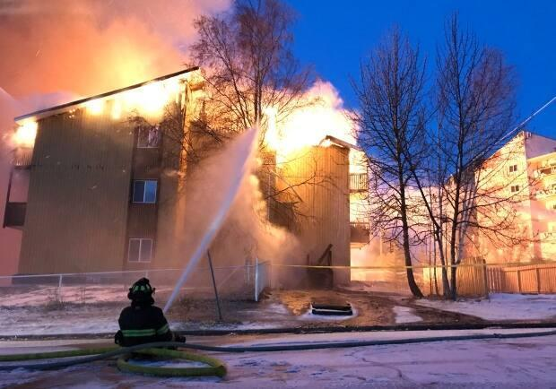 A firefighter fights the flames from the ground at Rockhill apartments in Yellowknife in 2018.