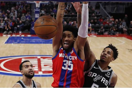 Detroit Pistons forward Christian Wood (35) dunks as San Antonio Spurs guard Dejounte Murray (5) defends during the second half of an NBA basketball game, Sunday, Dec. 1, 2019, in Detroit. (AP Photo/Carlos Osorio)