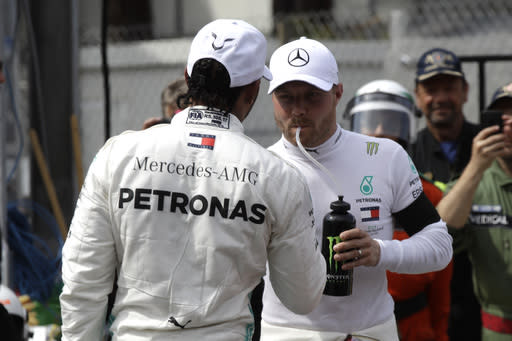 Mercedes driver Lewis Hamilton of Britain, left congratulates with his teammate driver Valtteri Bottas of Finland, after the qualifying session at the Monaco racetrack, in Monaco, Saturday, May 25, 2019. The Formula one race will be held on Sunday. (AP Photo/Luca Bruno)