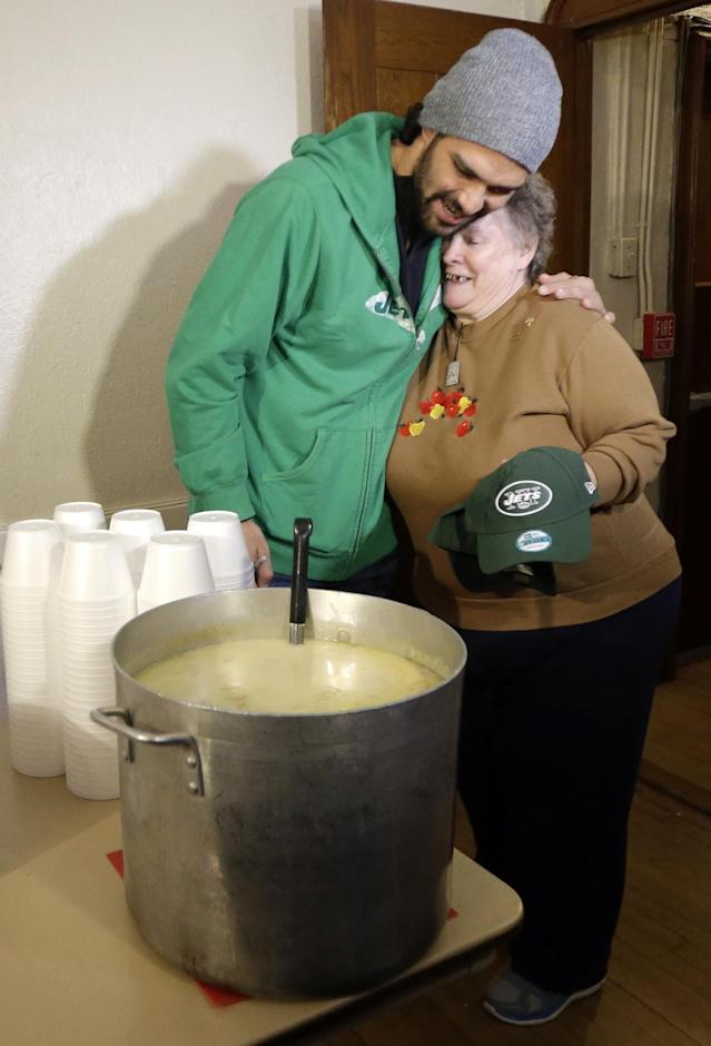 New York Jets NFL football quarterback Mark Sanchez, left, gives a hug to Nancy Sisco, 67, during a visit to the Community Soup Kitchen of Morristown as part of the team's Thanksgiving Day week celebration, Tuesday, Nov. 26, 2013, in Morristown, N.J. (AP Photo/Julio Cortez)