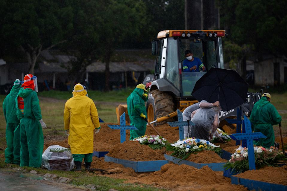 Relatives are surrounded by gravediggers as they attend a COVID-19 victim's funeral at the Nossa Senhora Aparecida cemetery in Manaus, Amazonas state, Brazil, on January 13, 2021, amid the novel coronavirus pandemic. - In Manaus there is a shortage of hospital beds as cases increased at an alarming rate. The city, with two million inhabitants, had already experienced nightmarish scenes in April and May, with mass graves and refrigerated trucks parked in front of hospitals to pile up the dead. But the situation is even worse in the beginning of 2021, since between January 1 and 11, at least 1,979 people were admitted to hospitals due to the virus, against 2,128 for the whole month of April, the worst since the start of the pandemic. (Photo by MICHAEL DANTAS / AFP) (Photo by MICHAEL DANTAS/AFP via Getty Images)