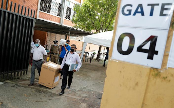 Sri Lankan polling officers carry election material as they dispatch them to polling centers ahead of the parliamentary elections in Colombo, Sri Lanka - Eranga Jayawardena/AP