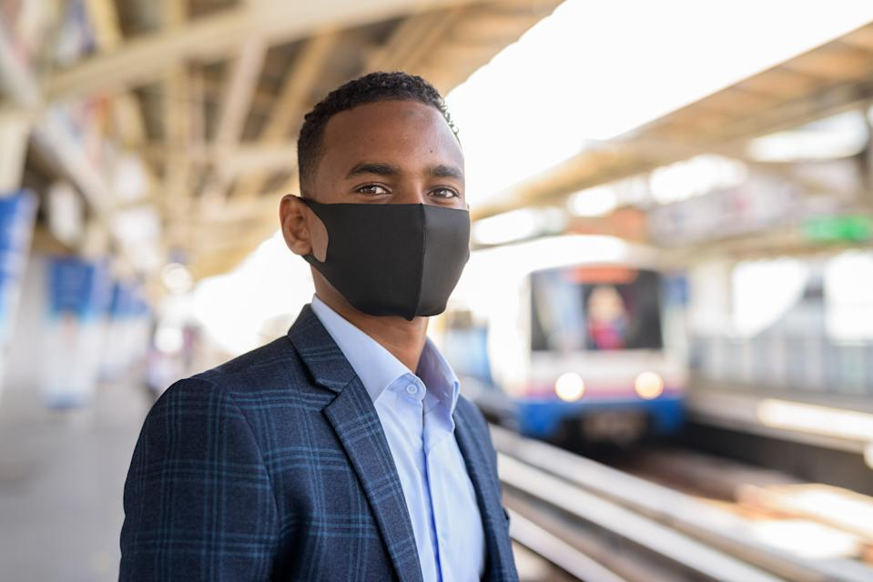 Portrait of young African businessman with mask for protection from corona virus outbreak at the sky train station