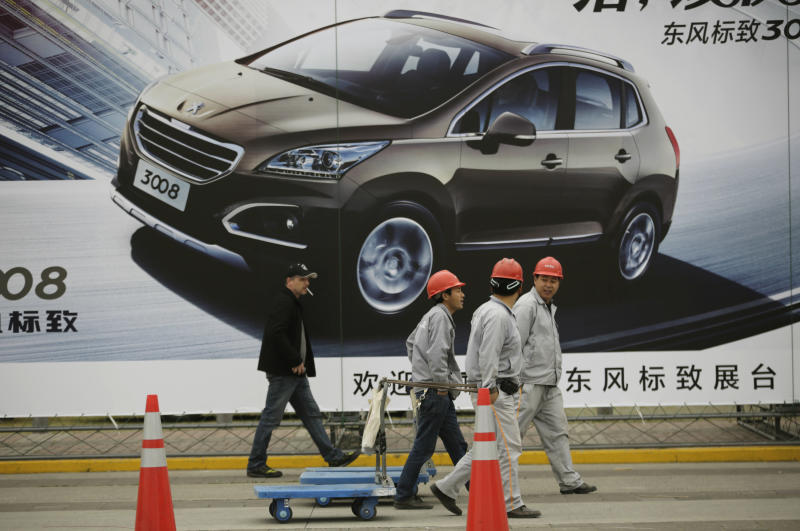 Workers walk past a poster of a car ahead of the Shanghai International Automobile Industry Exhibition (AUTO Shanghai) at the Shanghai International Exhibition Center in Shanghai, China Thursday, April 18, 2013. These should be good times for Chinese automakers as they prepare to show off their latest models at the Shanghai auto show. Their home market is the world's biggest and growing. But independent automakers such as Chery and Geely are being squeezed by bigger, richer global rivals including General Motors and Nissan that are creating low-priced models for local tastes. Domestic brands account for less than half of their own market. (AP Photo/Eugene Hoshiko)
