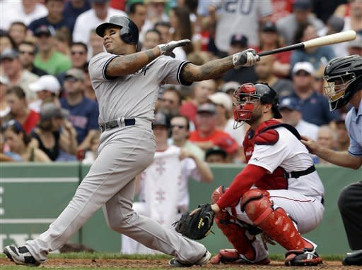 New York Yankees' Andruw Jones follows through on a solo home run as Boston Red Sox catcher Kelly Shoppach watches in the fourth inning of the first baseball game in a day-night doubleheader at Fenway Park in Boston Saturday, July 7, 2012. (AP Photo/Elise Amendola)