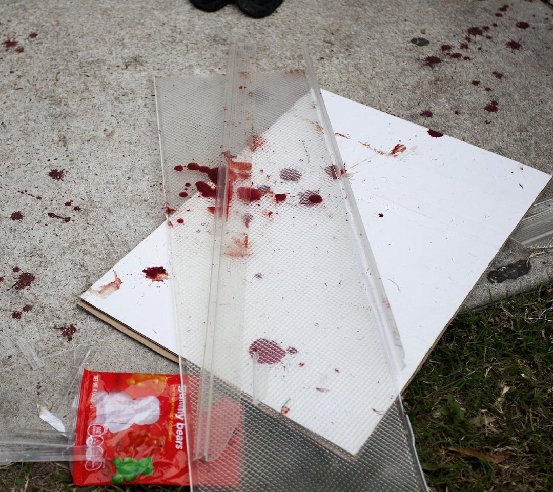 Bloody items that are left in the yard at 7318 Enchanted Creek in Cypress, Texas, Sunday, Nov. 10, 2013 after gunfire rang out Saturday night at a house party there, killing two and injuring at least 22, authorities said. Authorities say they're seeking two gunmen. (AP Photo/Bob Levey)