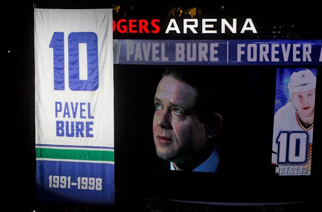Retired Vancouver Canucks forward Pavel Bure, of Russia, is displayed on a video screen as he watches his number 10 retired and lifted to the rafters during a ceremony before the Canucks NHL hockey game against the Toronto Maple Leafs in Vancouver, British Columbia, on Saturday Nov. 2, 2013. (AP Photo/The Canadian Press, Darryl Dyck)
