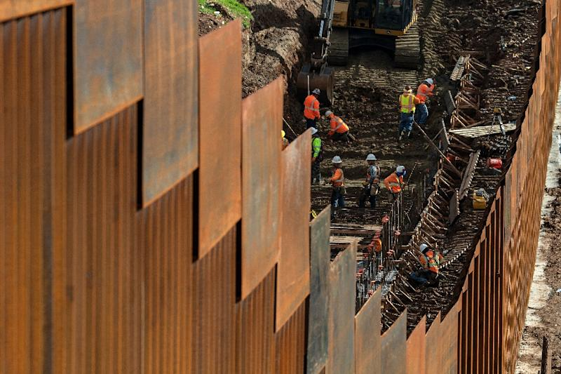 Workers reinforce a section of the US-Mexico border wall near Tijuana, Mexico (AFP Photo/Guillermo Arias)