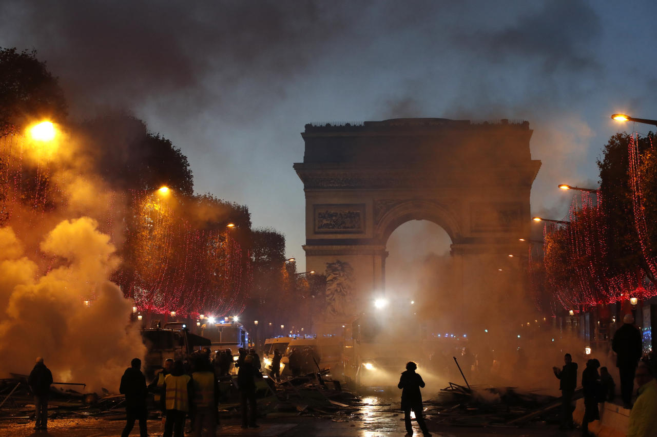 <p>Plumes of smoke are seen near the Arc de Triomphe on the Champs-Elysees avenue decorated with the Christmas lightings during a protest against tax Saturday, Nov. 24, 2018 in Paris. (Photo: Christophe Ena/AP) </p>