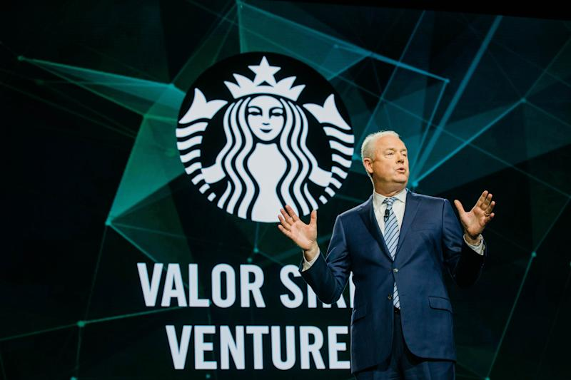 CEO Kevin Johnson speaks on a stage in front of the Starbucks logo and a sign saying Valor Siren Ventures.