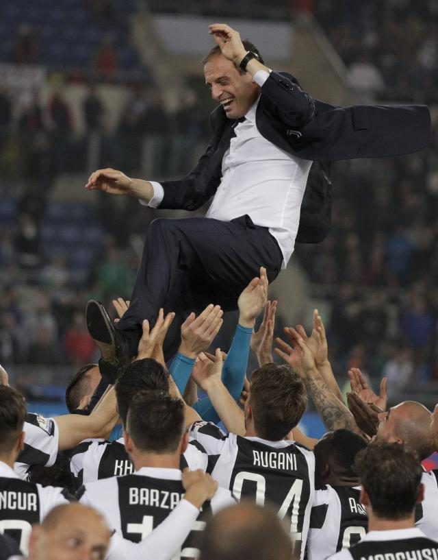 Juventus coach Massimiliano Allegri is thrown in the air as players celebrate their 4-0 win at the end of the Italian Cup final soccer match between Juventus and AC Milan, at the Rome Olympic stadium, Wednesday, May 9, 2018. (AP Photo/Gregorio Borgia)