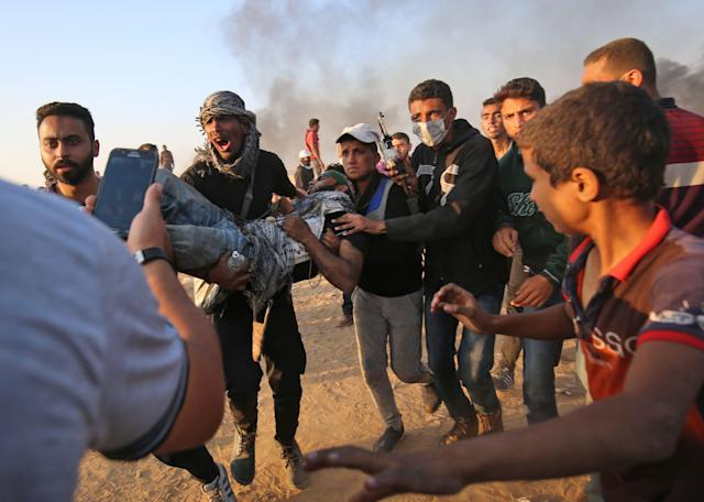 <p>Palestinians carry away a protester injured during clashes with Israeli forces along the border east of Khan Yunis in the southern Gaza Strip on May 15, 2018 after demonstrations marking 70th anniversary of Nakba — also known as Day of the Catastrophe in 1948 — and against the US' relocation of its embassy from Tel Aviv to Jerusalem. (Photo: Said Khatib/AFP/Getty Images) </p>