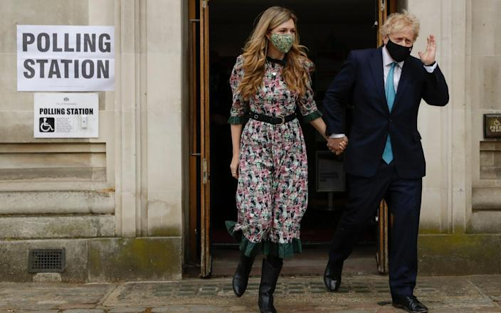 Boris Johnson leaves a polling station with his partner Carrie Symonds after casting his vote in local council elections in London - Matt Dunham/ AP