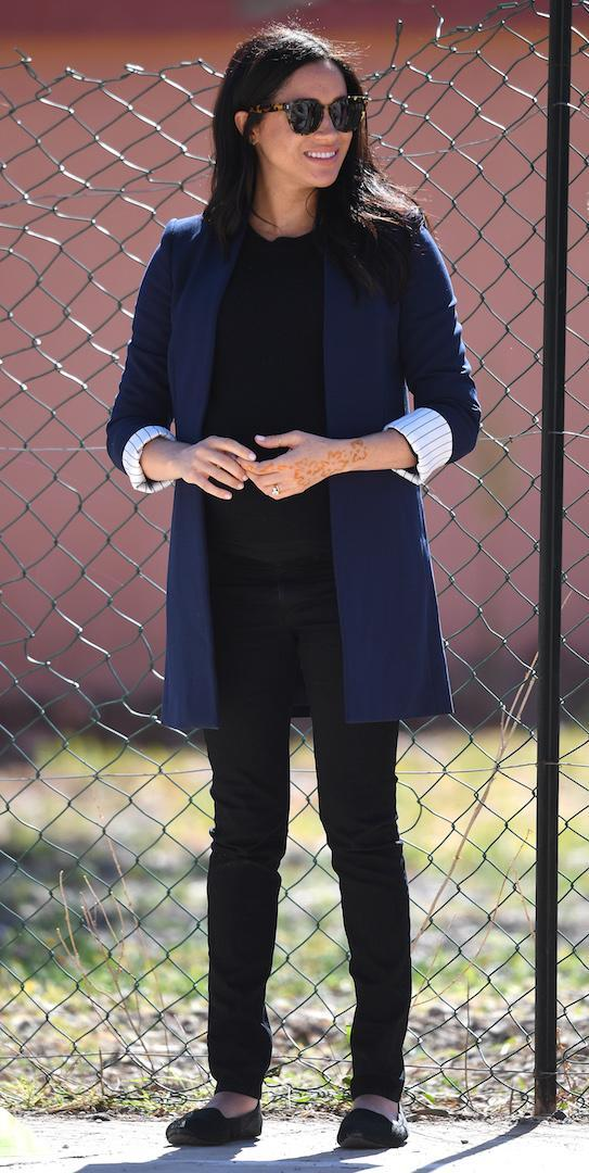 <p>For a day of engagements in the Atlas Mountains, Meghan wore a navy Alice + Olivia blazer with black Hatch skinny jeans and a matching cashmere sweater by Misha Nonoo. She ditched her signature heels for her Birdies slippers <em>[Photo: PA]</em> </p>