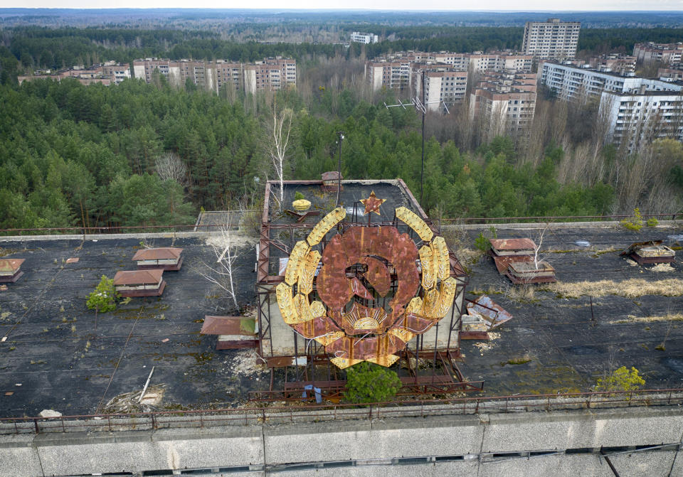 The rusty emblem of the Soviet Union is seen over the ghost town of Pripyat close to the Chernobyl nuclear plant, Ukraine, Thursday, April 15, 2021. The vast and empty Chernobyl Exclusion Zone around the site of the world's worst nuclear accident is a baleful monument to human mistakes. Yet 35 years after a power plant reactor exploded, Ukrainians also look to it for inspiration, solace and income. (AP Photo/Efrem Lukatsky)