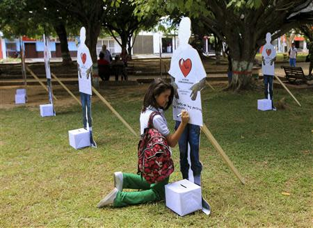 A student writes a message on a cut-out figure of an active rebel of the FARC during an event to campaign for FARC demobilisation in Tame, Arauca province, September 18, 2013. Colombia's Defence Minister Juan Carlos Pinzon and army chief commanders attended the event as part of the ongoing peace negotiation with FARC. REUTERS/Jose Miguel Gomez